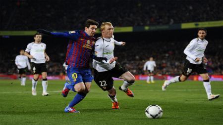 Lionel Messi (kiri) berhadapan dengan Jeremy Mathieu (kanan) saat masih membela Valencia. - INDOSPORT