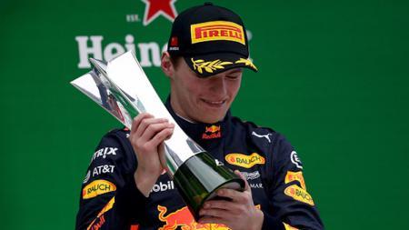 Max Verstappen memegang trofi setelah finish di urutan ketiga. - INDOSPORT