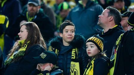 Fans Dortmund harap-harap cemas menunggu pengumuman dari panitia pertandingan. - INDOSPORT