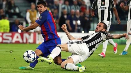Giorgio Chiellini tampak menjegal Luis Suarez pada pertandingan Liga Champions leg pertama. - INDOSPORT