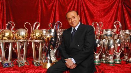 Silvio Berlusconi berfoto bersama dengan trofi-trofi yang ia raih saat menjadi presiden AC Milan. - INDOSPORT