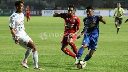 Gelandang sayap Persib Bandung, Febri Hariyadi (kanan) mencoba melewati kiper Arema FC, Kurnia Meiga Hermansyah (kiri) pada laga pembuka Liga 1 di Stadion Gelora Bandung Lautan Api (GBLA), Sabtu (15/04/17).