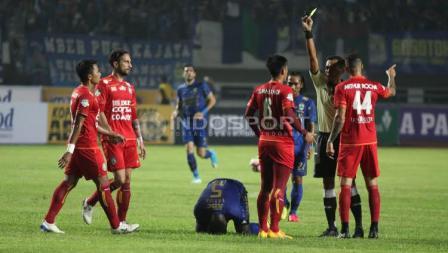 Marquee player Persib Bandung, Michael Essien (tengah) terjatuh usai dilanggar salah satu pemain Arema FC pada laga pembuka Liga 1 di Stadion Gelora Bandung Lautan Api (GBLA), Sabtu (15/04/17).