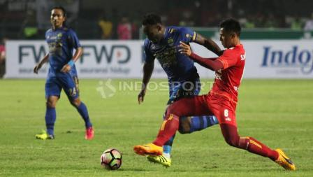 Marquee player Persib Bandung, Michael Essien (tengah) mencoba melewati pemain Arema FC pada laga pembuka Liga 1 di Stadion Gelora Bandung Lautan Api (GBLA), Sabtu (15/04/17).