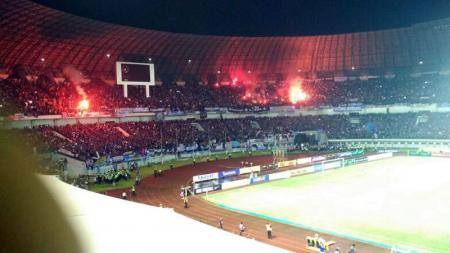 Sejumlah Bobotoh menyalakan flare diStadion Gelora Bandung Lautan Api usai laga antara Persib Bandung vs Arema FC. - INDOSPORT