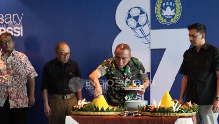 Ketua Umum PSSI memotong tumpeng dalam perayaan HUT PSSI.