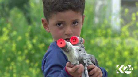 Anak kecil asal Irak yang bernama Messi, menodongkan pistol mainan. - INDOSPORT