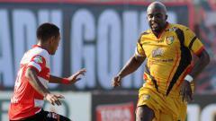 Indosport - Aksi Mohamed Sissoko berusaha melewati pemain Madura United di Stadion Gelora Ratu Pamelingan Kab. Pamekasan.