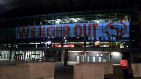 Lampu sorot Wenger Out terlihat di bagian samping Emirates Stadium. - INDOSPORT