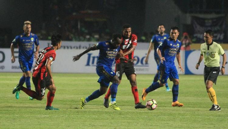 Michael Essien saat beraksi melewati hadangan para pemain Persipura Jayapura di pekan kelima Liga 1. Copyright: Muhammad Ginanjar/INDOSPORT