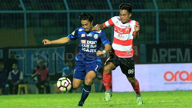 Bek kanan Arema FC, Benny Wahyudi sedang menjaga salah satu pemain Madura United. Copyright: Ian Setiawan/INDOSPORT