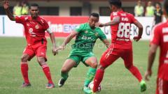 Indosport - Pemain Bhayangkara FC, Firman Utina (tengah) berebut bola dengan pemain Semen Padang, Irsyad Maulana.
