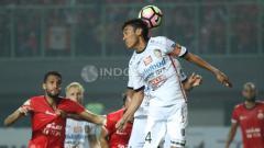 Indosport - Kapten Bali United, Fadil Sausu (tengah) mengahalau bola yang mengarah ke gawang Bali United dengan sundulan.