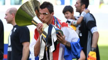 Mario Mandzukic mencium piala Serie A Italia. - INDOSPORT