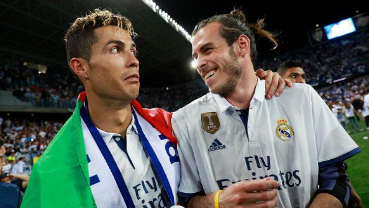Cristiano Ronaldo dan Gareth Bale berpose dalam perayaan gelar juara Real Madrid. Copyright: Gonzalo Arroyo Moreno/Getty Images