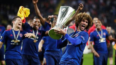 Momen Marouane Fellaini tengah selebrasi bersama trofi Liga Europa musim 2016/17. - INDOSPORT