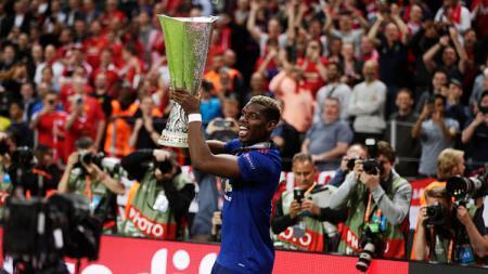 Paul Pogba tampak semangat dengan membawa trofi Liga Europa musim 2016/17 usai kalahkan Ajax Amsterdam. - INDOSPORT