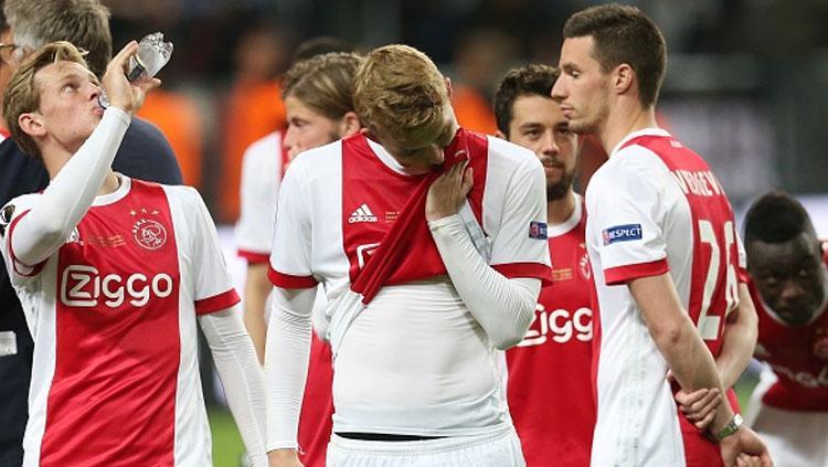 Frenkie de Jong (kiri), Matthijs de Ligt, dan Nick Viergever tampak lesu usai timnya dikalahkan Man United. Copyright: VI Images via Getty Images