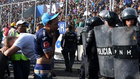 Polisi tampak berjaga ketat melawan fans yang nekat masuk stadion. - INDOSPORT