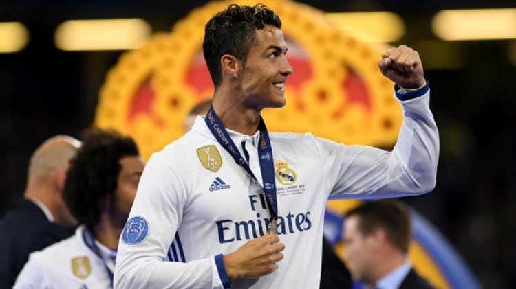 Cristiano Ronaldo berselebrasi pasca menerima medali juara Liga Champions. Copyright: Matthias Hangst / Staff
