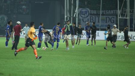 Bobotoh yang mengganggu jalannya laga dengan masuk ke lapangan menghampiri para pemain Persib Bandung. - INDOSPORT
