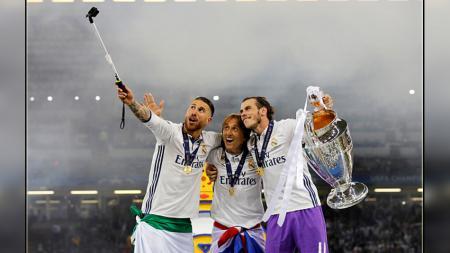 Tiga bintang Real Madrid, Sergio Ramos (kiri), Luka Modric (tengah), dan Gareth Bale berfoto bersama dengan trofi Liga Champions. - INDOSPORT