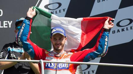 Andrea Dovizioso kibarkan bendera Italia. - INDOSPORT