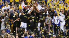 Indosport - Selebrasi pemain Golden State Warriors saat mengangkat trofi NBA musim 2016/17 di Oracle Arena.