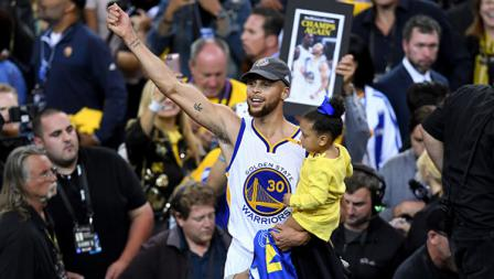 Stephen Curry menggendong anaknya, Riley Curry saat merayakan kemenangan Golden State Warriors.