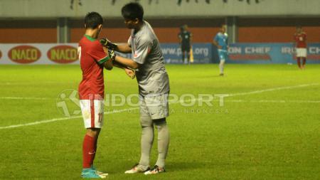 Kiper Timnas Indonesia, Kurnia Meiga Hermansyah (kanan) memakaikan ban kapten ke lengan Irfan Bachdim. - INDOSPORT
