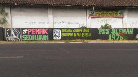 Mural bertuliskan pesan #PenakSeduluran. - INDOSPORT