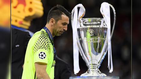 Ekspresi kecewa kiper Juventus, Gianluigi Buffon saat melewati trofi Liga Champions 2016/17. - INDOSPORT