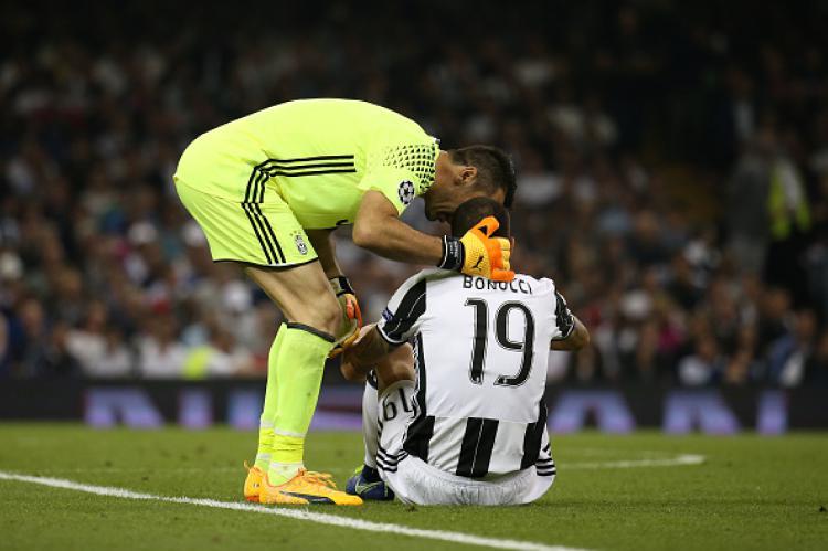 Gianluigi Buffon memberikan semangat kepada rekan setimnya, Leonardo Bonucci saat Juventus gagal meraih gelar Liga Champions 2016/17. Copyright: INDOSPORT