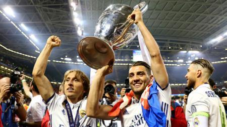 Mateo Kovacic (kanan) mengangkat trofi Liga Champions bersama dengan Luka Modric. - INDOSPORT