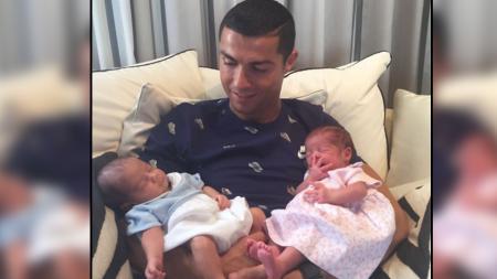 Cristiano Ronaldo dan dua anak kembarnya. - INDOSPORT