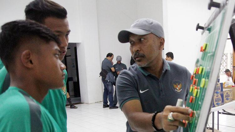 Fakhri Husaini saat menyusun formasin bersama dua pemain Timnas U-16. Copyright: Dewo/PSSI