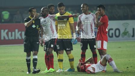 Seorang pemain Persija Jakarta terkapar di atas tanah.