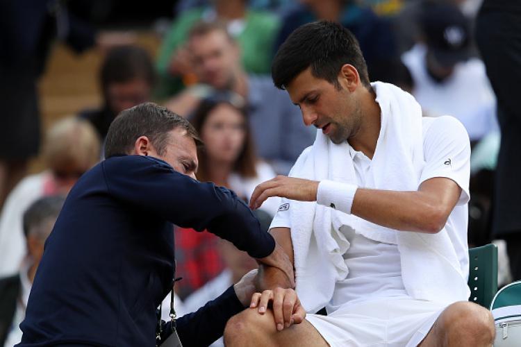 Novak Djokovic saat sedang diobati oleh tim medis. Copyright: INDOSPORT