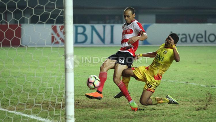 Peter Odemwingie menendang bola ke gawang Madura United. Copyright: Herry Ibrahim/INDOSPORT