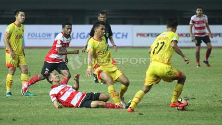 Indra Kahfi berusaha lepas dari hadangan pemain Madura United.