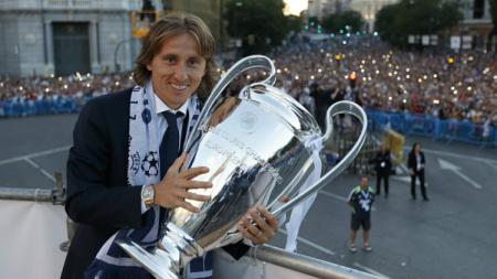 Luka Modric berpose bersama trofi Liga Champions. - INDOSPORT