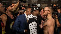 Indosport - Conor McGregor dan Floyd Mayweather saat lakukan konferensi pers.
