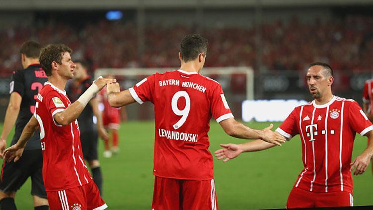 Robert Lewandowski melakukan selebrasi bersama Thomas Mueller (kiri) dan Franck Ribery. Copyright: INDOSPORT