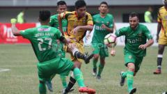 Indosport - Zikri Akbar (tengah) saat mengeksekusi bola ke arah gawang Bhayangkara FC. FOTO INDOSPORT/Herry Ibrahim.