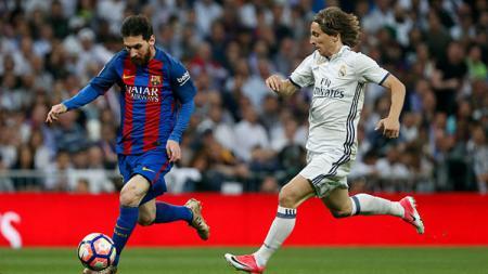 Lionel Messi ketika dikawal Luca Modric dalam laga El Clasico musim lalu. - INDOSPORT