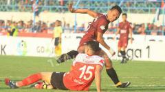 Indosport - Ferdinand Sinaga sampai terjengkang setelah bola berhasil disapu bersih Fabiano Beltrame. FOTO: Ian Setiawan/Indosport.com