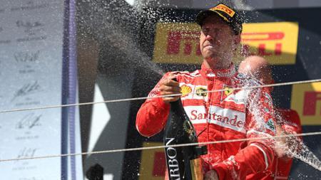 Sebastian Vettel selebrasi dengan menyemprotkan bir. - INDOSPORT