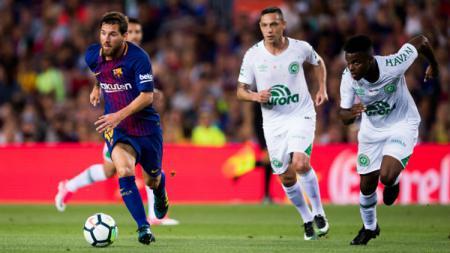 Pemain Chapecoense terlihat kesulitan menghentikan laju Lionel Messi. - INDOSPORT