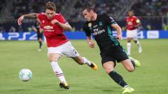 Indosport - Victor Lindelof (kiri) mendapat kawalan ketat dari Gareth Bale.