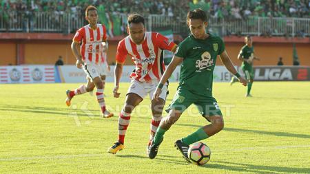 Duel perebutan antara pemain Persepam menghadapi Persebaya Surabaya. - INDOSPORT